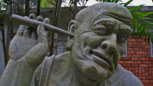 Statue of Fellow Scratching His Ear With a Stick